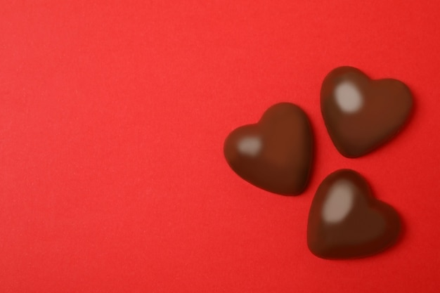 Chocolate hearts on red background, space for text