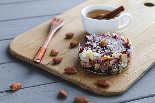 Chocolate homemade cake brownie with cocoa, almond and cherry on rustic wooden board with cup of tea side view