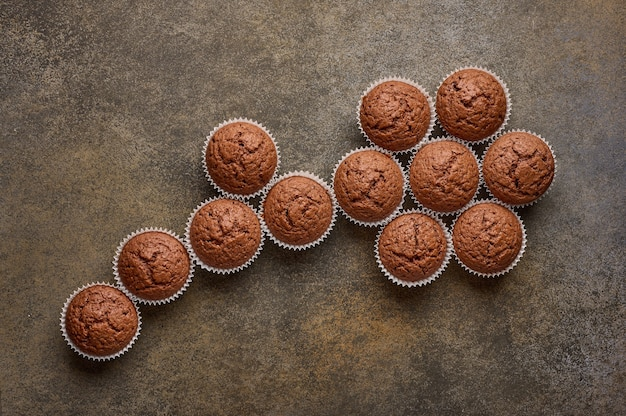 Chocolate homemade cupcakes are lined with flower shapes, copy space, top view