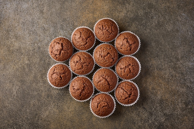 Chocolate homemade cupcakes laid out in the form of honeycomb on wooden surface, copy space, top