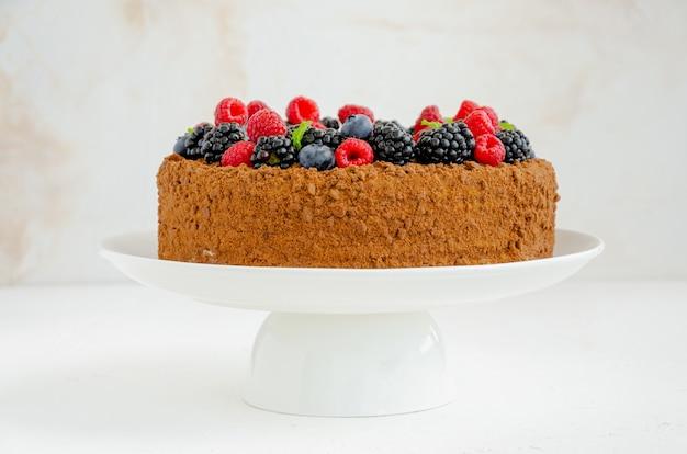 Шоколадно-медовый торт со сливками и свежими ягодами. скопируйте пространство.