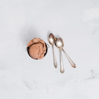 Chocolate ice cream in bowl with spoons on marble surface