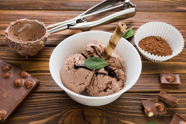 Chocolate ice cream in bowl on wooden table