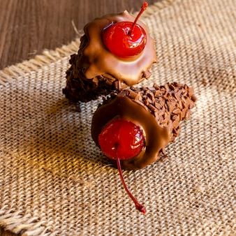 Chocolate ice cream cone with a cherry on top on rustic wooden background