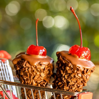 Chocolate ice cream cones with a cherry on top on shopping cart on rustic wooden background close up