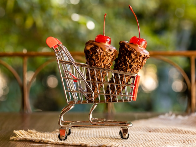 Chocolate ice cream cones with a cherry on top on a shopping cart on rustic wooden background