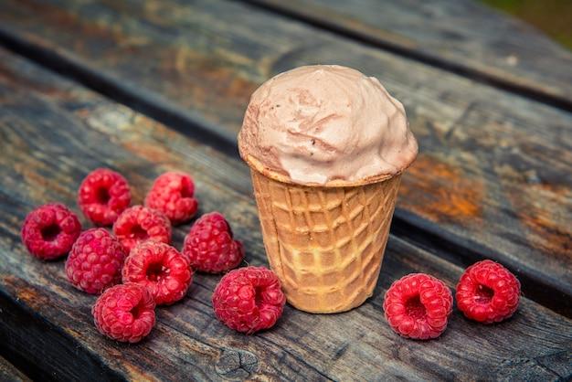 Шоколадное мороженое в вафельном стаканчике с ягодами малины на деревянном столе