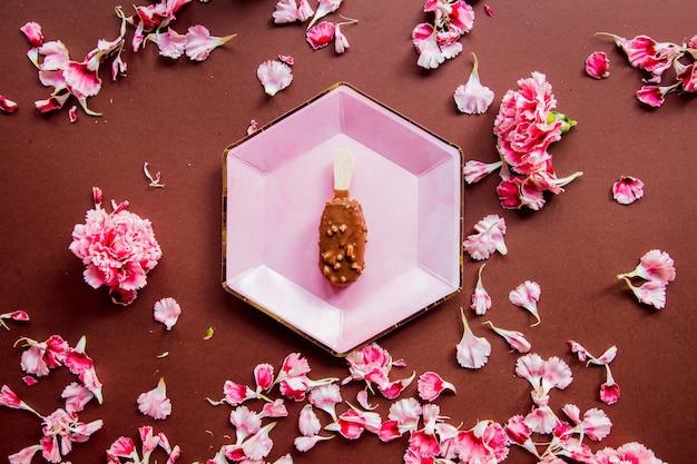 갈색 바탕에 패 랭이 꽃잎과 함께 접시에 초콜릿 아이스크림