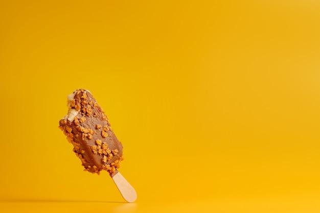 黄色の背景にチョコレートアイスクリームのアイスキャンディーがかまれた