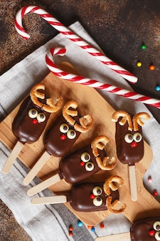 Chocolate ice cream on a stick with a christmas deer face with candy red nose