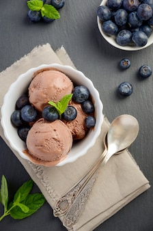 Chocolate ice cream with blueberries on black slate background top view flat lay