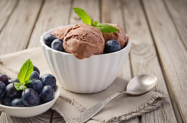 素朴な木製の背景の白いボウルにブルーベリーとチョコレートアイスクリーム
