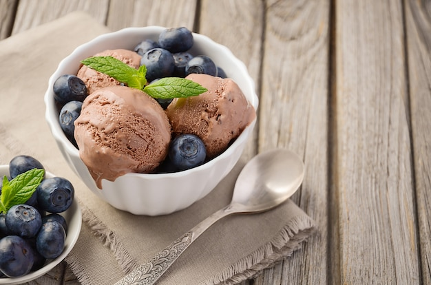 Chocolate ice cream with blueberries on rustic wooden