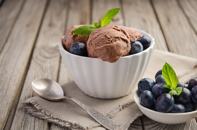 Chocolate ice cream with blueberries in white bowl on rustic wooden table.