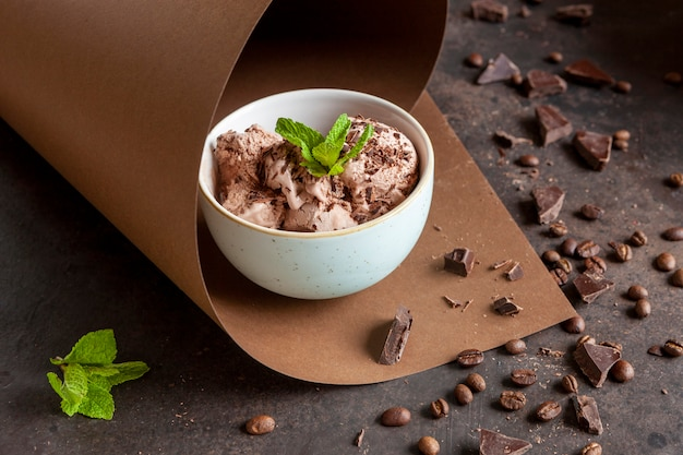 Chocolate ice cream with chocolate chips, coffee beans and fresh mint in paper swirl