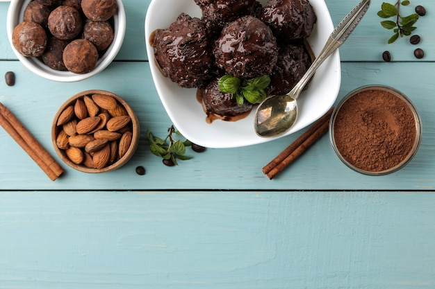 青い木製のテーブルに液体チョコレートとシナモンスティック、コーヒー豆、アーモンドを添えたチョコレートアイスクリーム。上面図