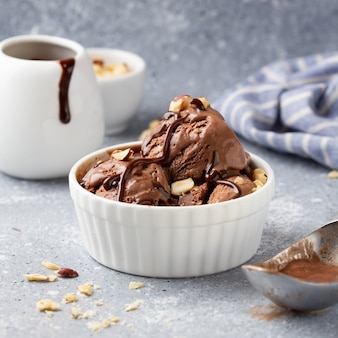 Chocolate ice cream with sauce and nuts, delicious summer dessert