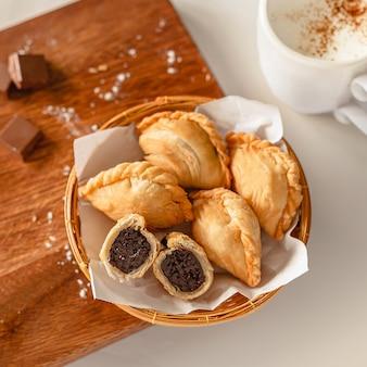 나무 커팅 보드와 재료에 퍼프 페스트리와 커피 컵 안에 초콜릿