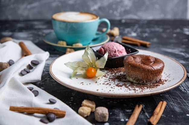 Chocolate lava cake molten with ice cream on plate and cappuccino. balls of ice cream in cup . dark black space.