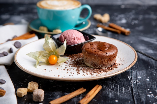 Chocolate lava cake molten with ice cream on plate and cappuccino. balls of ice cream in cup . dark black wall.