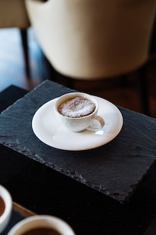 Chocolate lava cake topping with icing sugar inside white ceramic cup.