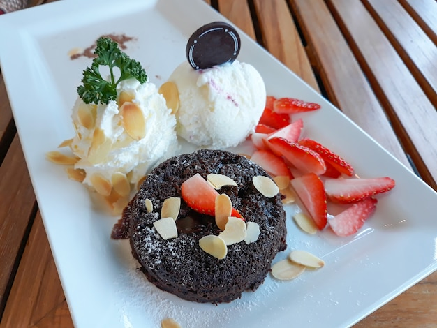 Chocolate lava cake with icecream and fresh fruit on white plate.