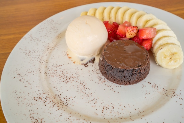 Chocolate lava cake with vanilla icecream, strawberry and banana topping