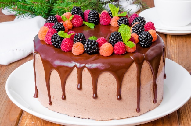 Chocolate layer cake with cherry filling and fresh berries on top of the new year and christmas