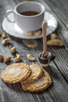 Chocolate lolly in the shape of a small cup with a cup of tea and nuts on wood