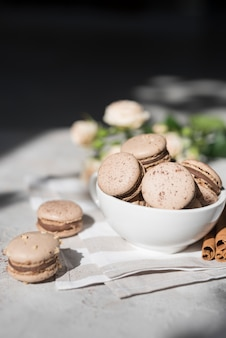 Chocolate macaroons in ceramic bowl over the napkin