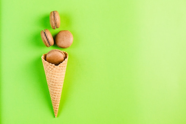 Chocolate macaroons in a waffle cone on a green copyspace, top view, flatley with copyspace