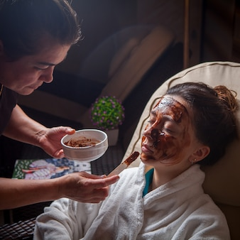 Chocolate mask with woman and master on beauty saloon