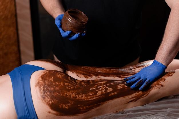 젊은 여자의 다리와 엉덩이를위한 초콜릿 마사지. 초콜릿 랩 스파 트리트먼트.