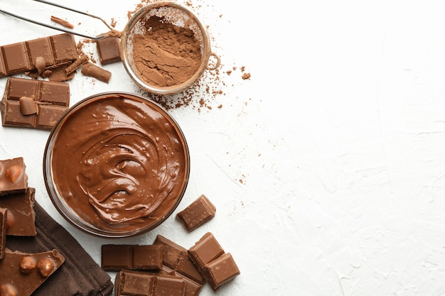 Chocolate, melted chocolate and powder on white background