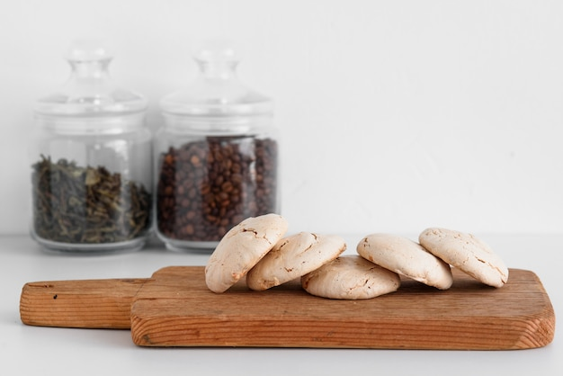 Шоколадные безе лежат на деревянной доске в линию. кофе и чай в стене. итальянский и французский десерт.
