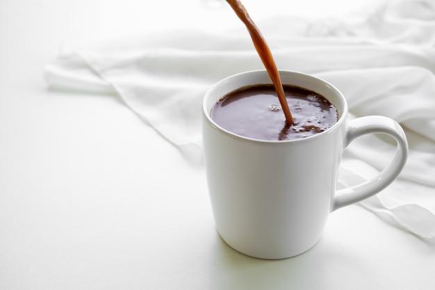 チョコレートミルクカップ、コピースペースのある白い背景にフラットレイホットココ、朝食やリラックスした時間のための健康的な飲み物、世界のチョコレートの日。