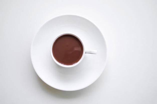 チョコレートミルクカップフラットは、コピースペースで白い背景にホットココを置きました