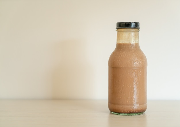 Chocolate milk in glass bottle on table