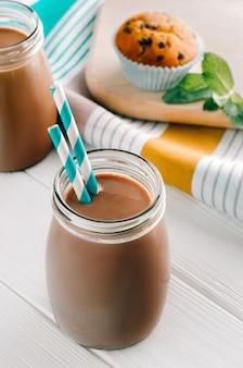 ターコイズブルーのストローとボトルのチョコレートミルク