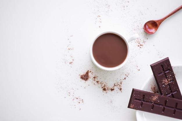 白い背景の上の聖霊降臨祭のプレートにバーチョコレートと白いカップのチョコレートミルク