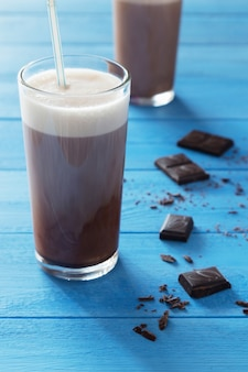 Chocolate milk shake and chocolate crumbs on blue wooden background