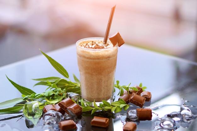 Шоколадный молочный коктейль со свежей мятой и льдом на стеклянном столе с размытым фоном