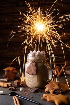 Шоколадное молоко с шоколадом, корицей и зефиром с бенгальским огнем на деревянном столе