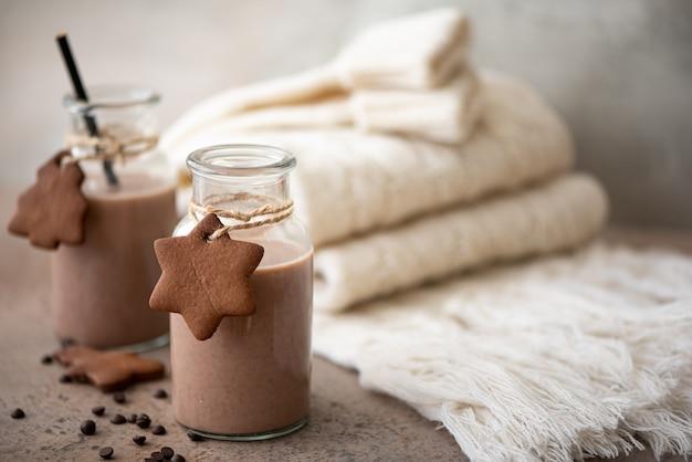 Шоколадное молоко с печеньем и тёплым вязанным шарфом на столе