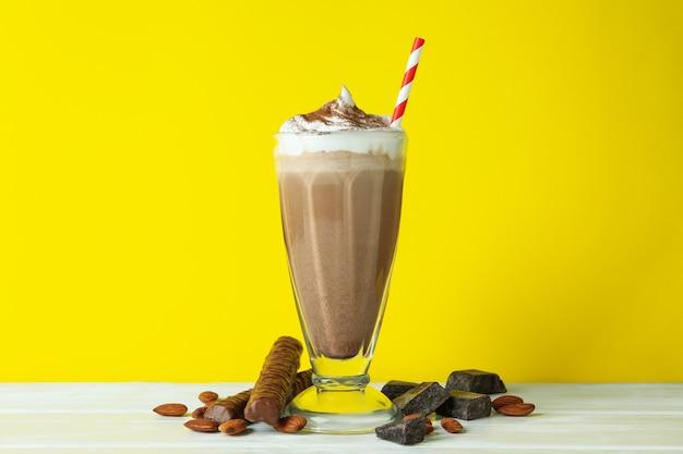 Chocolate milkshake, almond and chocolate against yellow wall