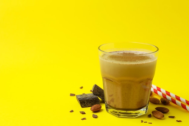 Chocolate milkshake, almond, chocolate and straws on yellow wall