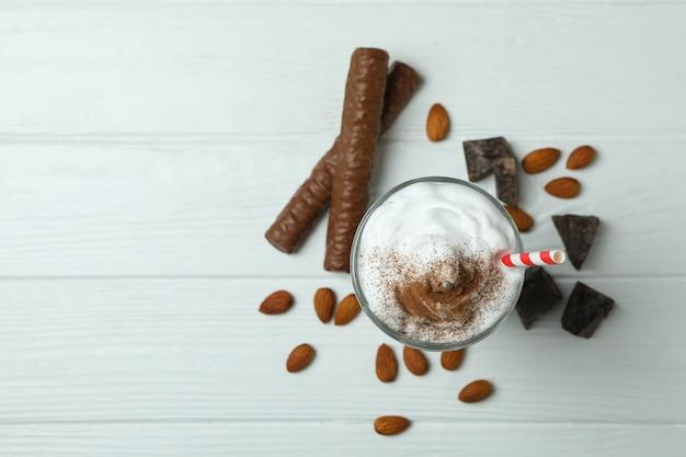 Chocolate milkshake, chocolate and almond on white wooden wall
