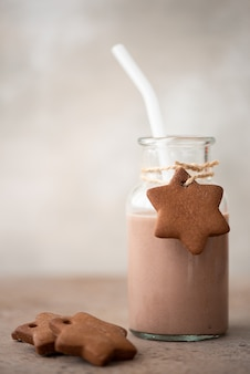 Chocolate milkshake in glass bottle with gingerbread crumbly cookies on table