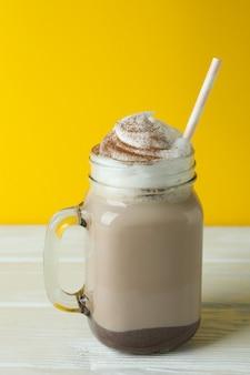 Шоколадный молочный коктейль на деревянном столе у желтой стены