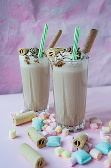 Chocolate milkshake with ice cream and whipped cream, marshmallows, cookies, waffles, served in a glass cup.